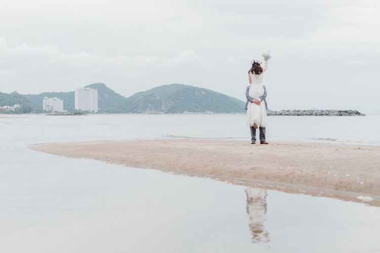wedding on the beach Adult Architecture Beach Beauty In Nature Casual Clothing Day Full Length Leisure Activity Lifestyles Nature One Person Outdoors Real People Rear View Reflection Sky Standing Water Women
