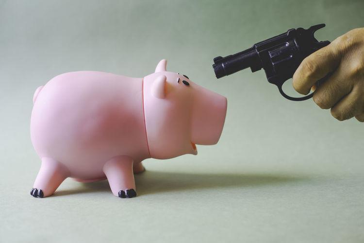 man with a gun and piggy bank. Concept of money problems Piggy Bank Piggy Piggybank Pink Color Pink Piggy Bank Coin Business Save Savings Money Money Box Gun Pistol Finance Crime Weapon Animal