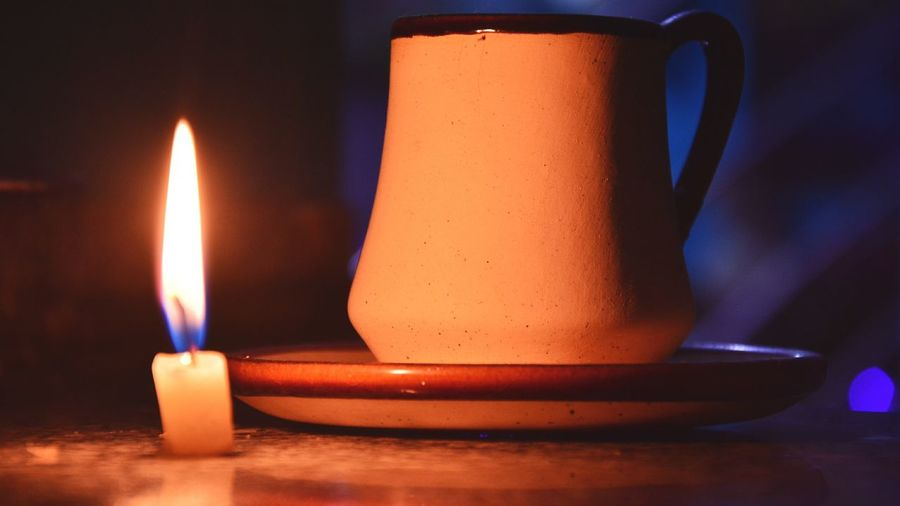 Close-Up Of Illuminated Candle By Cup On Table In Darkroom