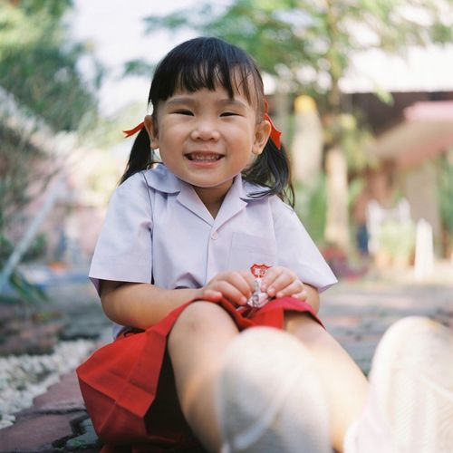 Portrait of smiling girl sitting outdoors