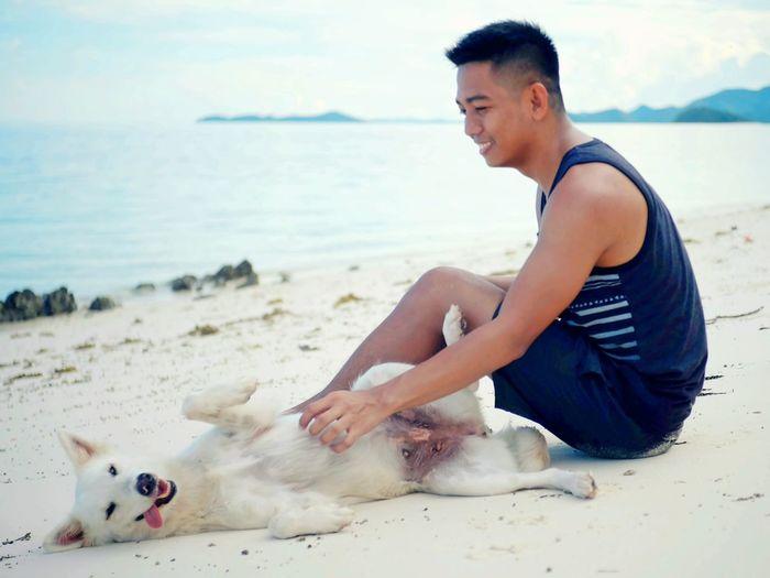 Man with dog sitting on beach against sky