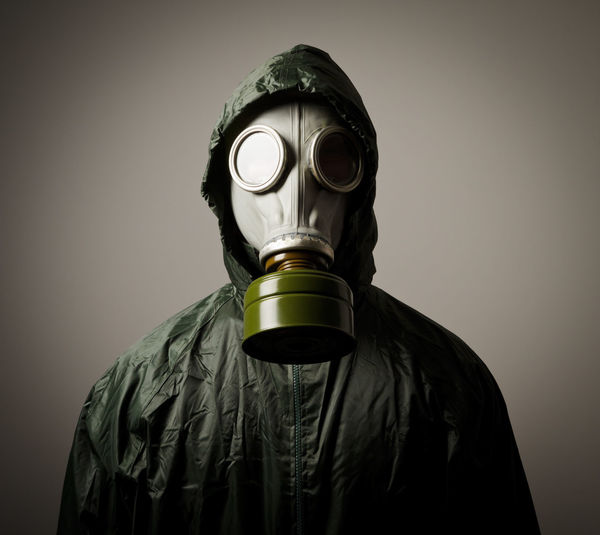 Portrait of person wearing gas mask while standing against gray background