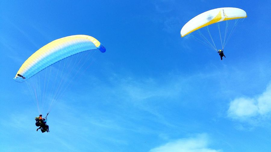 LOW ANGLE VIEW OF PARAPLANES AGAINST BLUE SKY