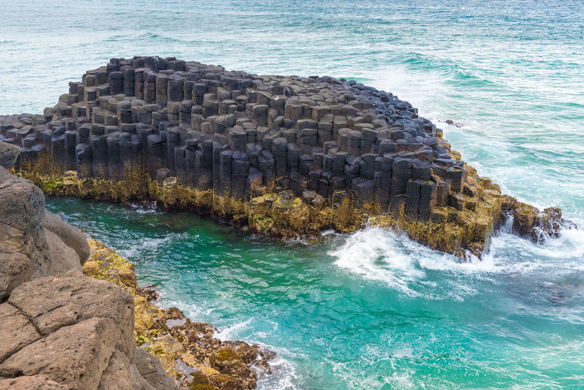 Crescent shaped hexagonal rock formations at Fingal Head, Australia Australia Australian Green Rock Formation View Beauty In Nature Cliff Crescent Shape Fingal Head Hexagonal Landmark Landscape Landscapes Lava Rocks Motion Nature Ocean Queensland Rock Scenics - Nature Sea Water Wave Yellow