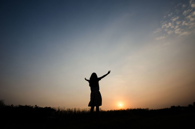 Silhouette woman with arms outstretched standing on land against sky during sunset