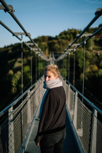 Portrait of woman on footbridge against sky
