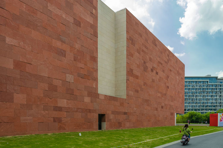 Brick wall by building against sky