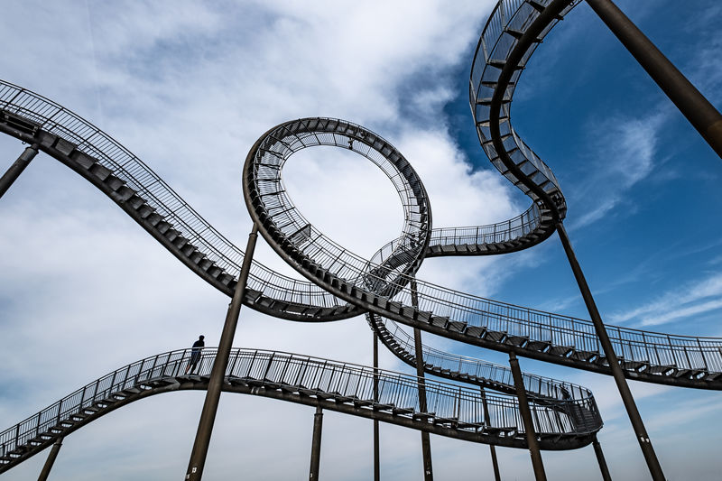 Low angle view of man in rollercoaster against sky