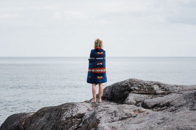 Rear view of woman standing on rock by sea against sky