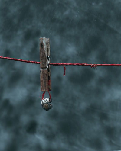 Close-up of clothespins on rope against sky