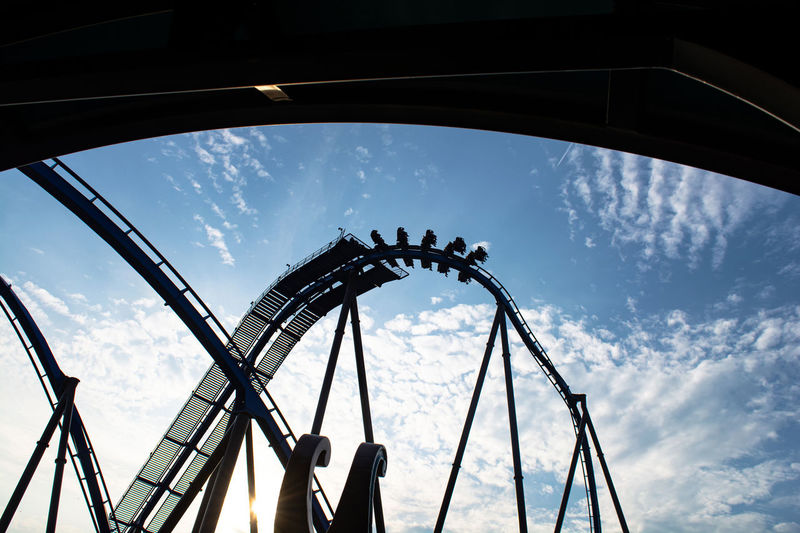 Low angle view of silhouette rollercoaster against sky