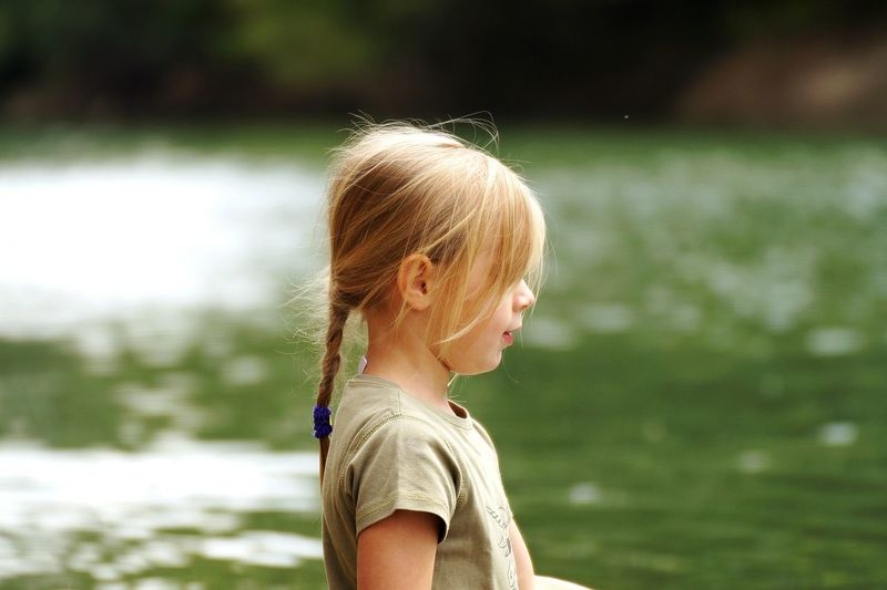 Side view of girl standing against lake