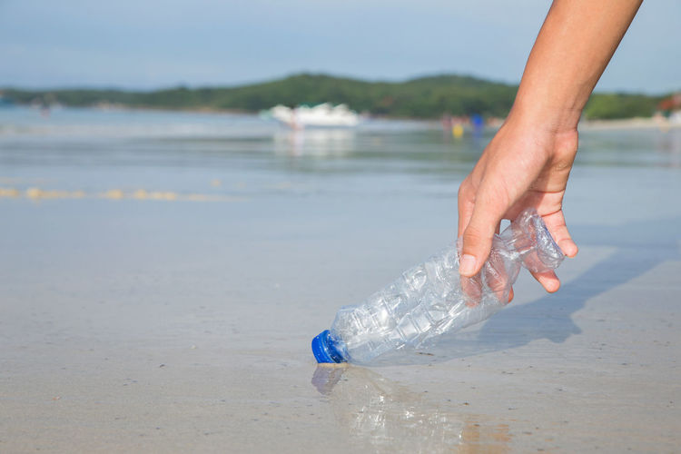 Person holding bottle on beach