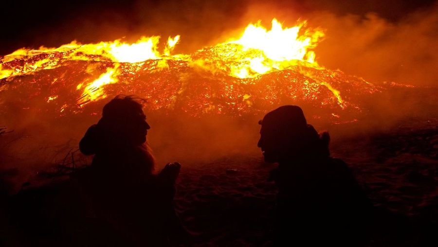 Silhouette man and woman sitting in front of large bonfire
