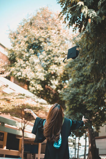 Rear view of woman catching mortarboard against trees
