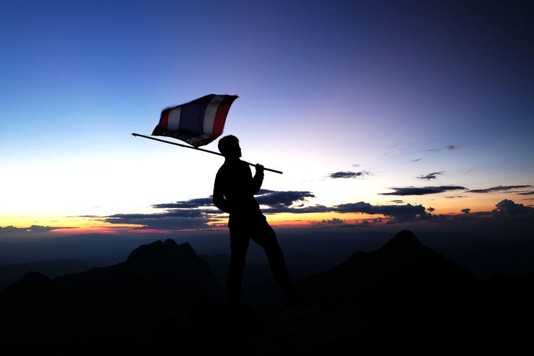 Silhouette person holding thai flag against sky during sunset