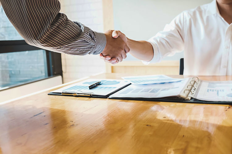 Close-up of business colleagues shaking hands at desk in office
