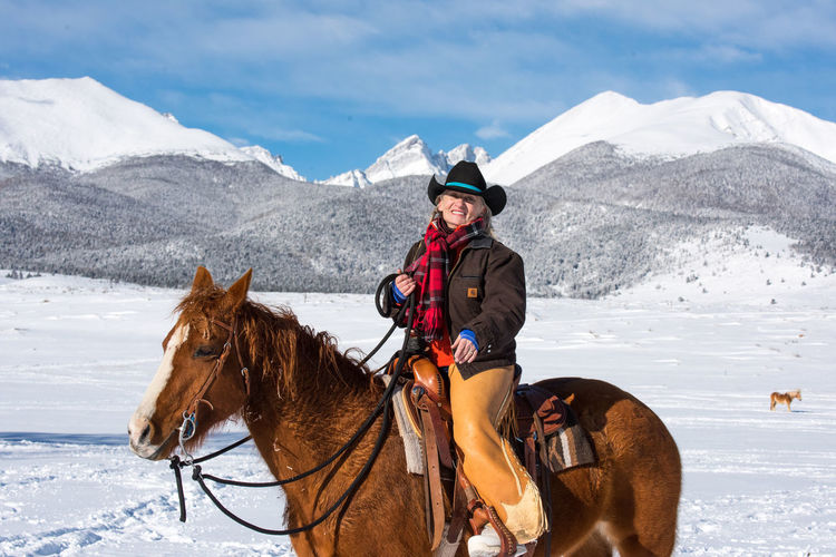 Colorado Winter Snowcapped Mountain Mountain Range Warm Clothing Outdoors Riding Ride One Animal Mountain Cold Temperature Horse Livestock One Person Snow Animal Themes Domestic Animals Ranch Life Horse Themes Cowgirl Cowboy Cowboy Hat Chaps Rope Scarf