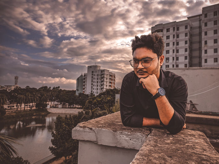 Young man sitting in city against sky
