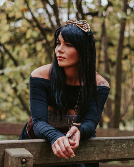 Young steampunk woman looking away while leaning on railing
