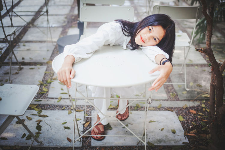 Portrait of a girl sitting on white table and white background