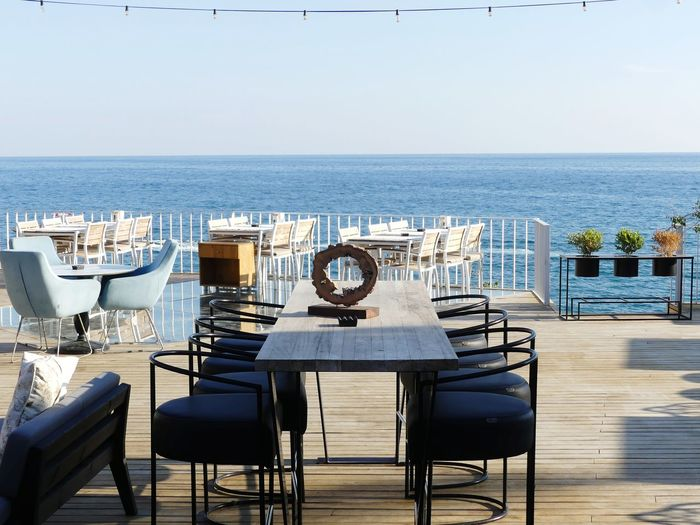 Chairs and tables at restaurant by sea against sky