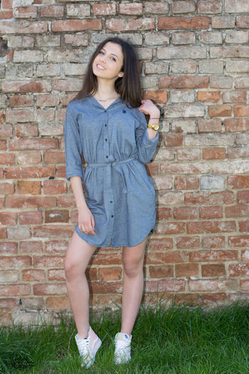 Adult Adults Only Beautiful Woman Brick Wall Casual Clothing Childhood Day Front View Full Length Lifestyles Long Hair Looking At Camera One Person One Woman Only One Young Woman Only Outdoors People Portrait Smiling Standing Young Adult Young Women