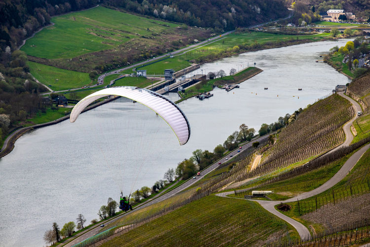 Flying paraglider over the valley of river moselle and over vineyards
