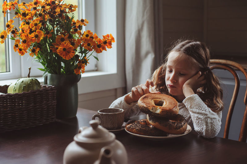 child girl having breakfast at home in autumn morning. Real life cozy modern interior in country house. Breakfast Homely Morning Rustic Bagel Breakfast Child Childhood Country Life Cozy Cute Drink Food Food And Drink Girls Home Interior House Indoors  Kid Lifestyles One Person Real People Table Wooden