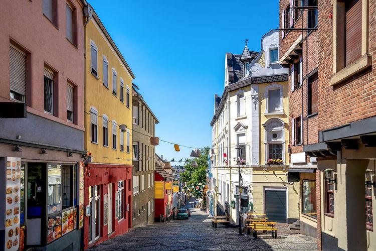Narrow street amidst buildings against blue sky