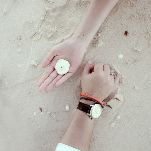 Cropped hands of people lying on sand at beach