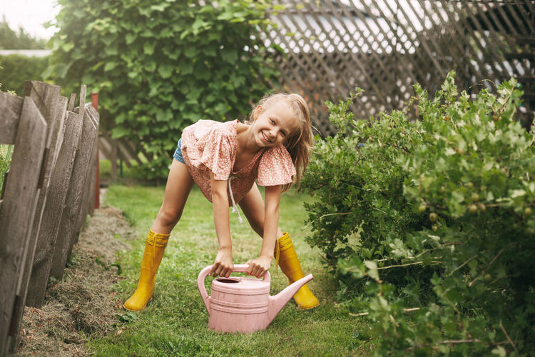 Portrait of smiling girl holding watering can on land in yard
