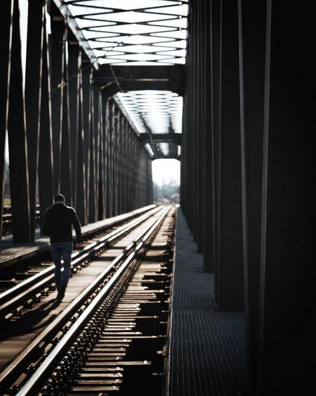 Rear view of man walking on railroad tracks
