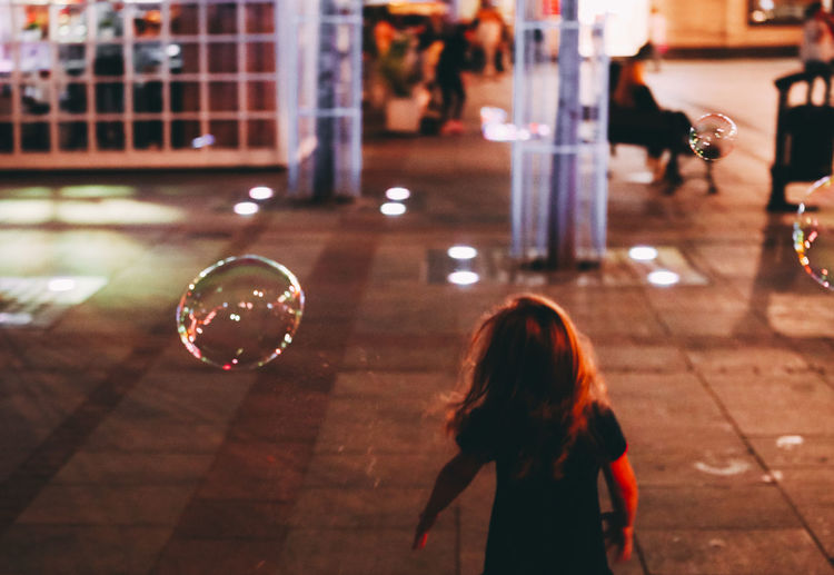 Architecture Bubble Bubble Wand Building Exterior Childhood Focus On Foreground Fragility Girls Illuminated Indoors  Leica Leicacamera Leisure Activity Lifestyles Magnumphotos Night One Person People Real People Women