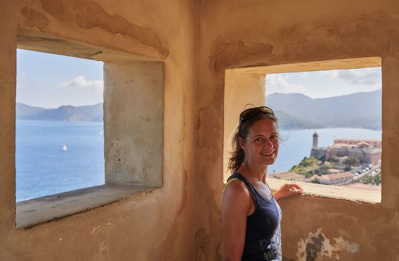 Portrait of smiling woman standing by sea against window