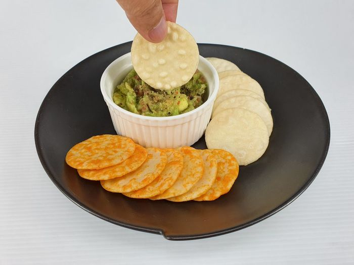 Close-up of hand holding food in plate