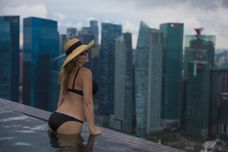 Woman Swimming In Infinity Pool Against Buildings