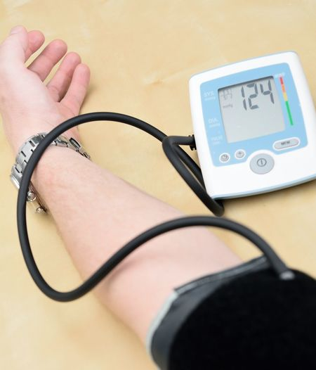 Cropped hand of man with blood pressure gauge on table at medical clinic