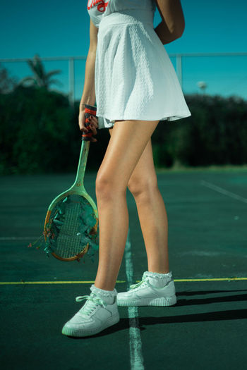 Low section of young woman standing in tennis court