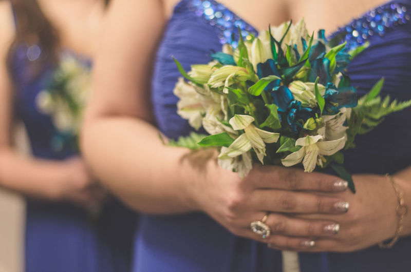 Midsection of two bridesmaids holding flowers