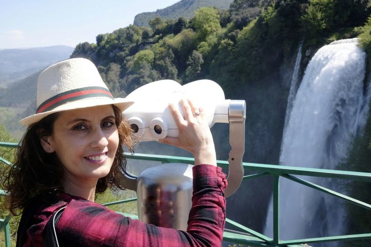 The girl admires Marmore waterfalls with binoculars One Person Smiling Young Adult Day Young Women Emotion Women Binoculars Tourist Waterfall Marmore Umbria, Italy Hat Real People Portrait Nature Outdoors Happiness