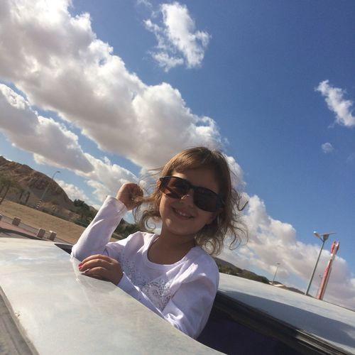 Portrait of smiling girl peeking from car sun roof