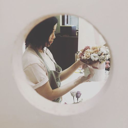 Woman holding bouquet seen through hole at flower shop
