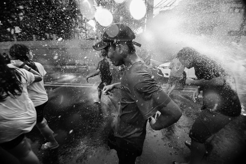 WHATTA! WHATTA! Passersby are sprayed with water using a water canon in San Juan City, Metro Manila on 24 June 2017 as the city celebrates Whatta Whatta Festival, an annual commemoration of the Feast of St. John The Baptist, who baptized Jesus Christ. The celebration is popularly done by splashing each other including passersby with water. On 2012, former City Mayor JV Ejercito changed the name of the festival from Feast of St. John the Baptist to Whatta Whatta. | The Photojournalist - 2017 EyeEm Awards People Larrymonseratepiojo Black And White Philippines EyeEm Philippines 👍 EyeEmBestPics The Human Condition EyeEm Best Shots The Week On EyeEm Everybodystreet Untold Stories Documentary Photography Water Wet Men Crowd Lifestyles Large Group Of People