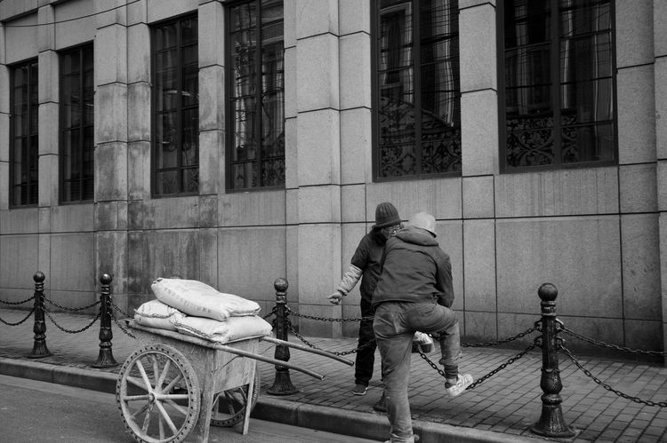 Building Exterior Architecture Built Structure City Real People Rear View Transportation Street Men One Person Mode Of Transportation Building Full Length Day Lifestyles Land Vehicle Cart City Life Bicycle Outdoors Blackandwhite Balck And White