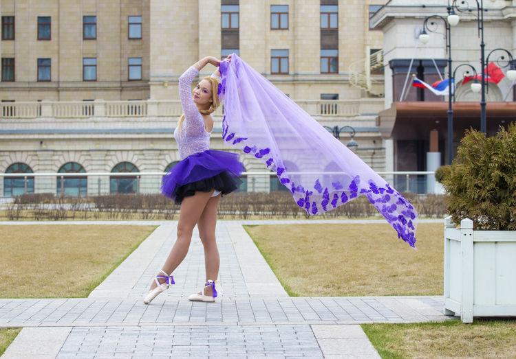 Full length of woman dancing against building
