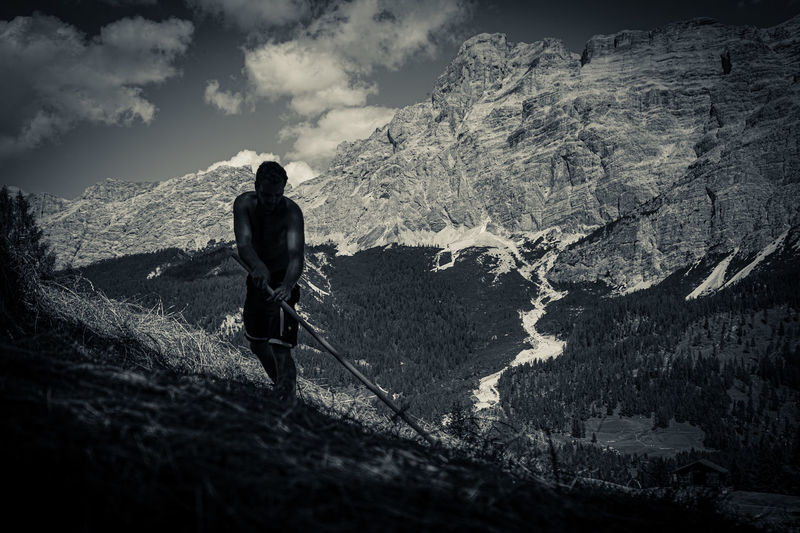 Rear view of man walking on mountain against sky