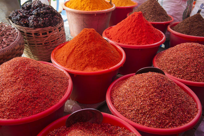 High angle view of ground spices in containers at market for sale