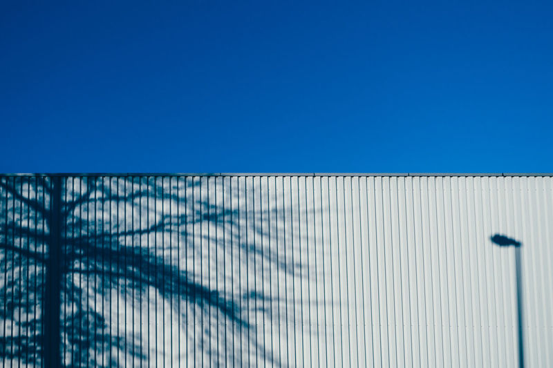 Shadow of tree and street light corrugated wall against clear blue sky