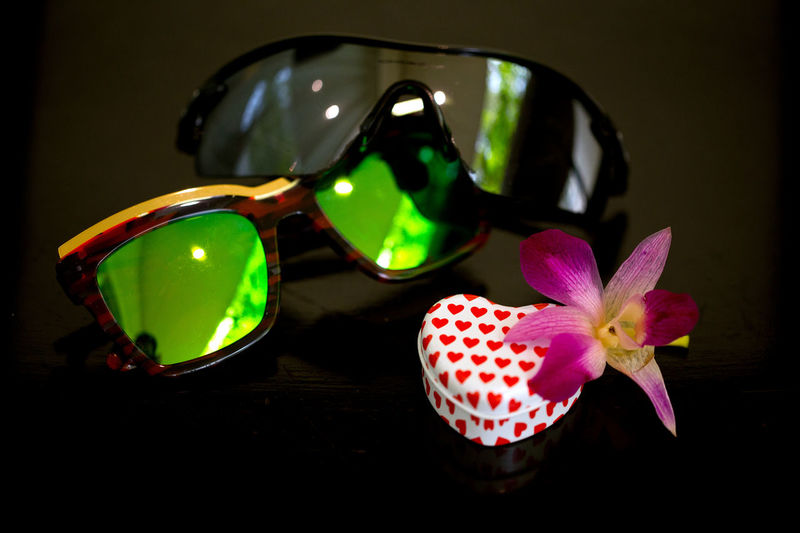 Two pairs of sun glasses decorated with a love metal box and orchid flower Flower Glasses Close-up Flowering Plant Sunglasses Beauty In Nature Plant Vulnerability  Fragility No People Freshness Pink Color Still Life Table Indoors  Reflection Fashion Petal Nature Focus On Foreground Personal Accessory Flower Head Eyewear